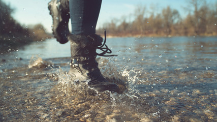 LOW ANGLE, DOF: Girl in black waterproof boots splashing the clear lake water.