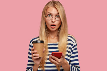 Photo of surprised blonde young woman with surprised facial expression, uses mobile phone for surfing internet, reads terrible news on web page, opens mouth from wonderment, drinks cappuccino