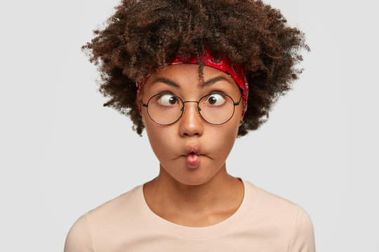 Close up portrait of funny African American girl makes grimace, crosses eyes purses lips, foolishes indoor, has bushy hair wears round spectacles isolated over white background. Ethnicity, fun concept