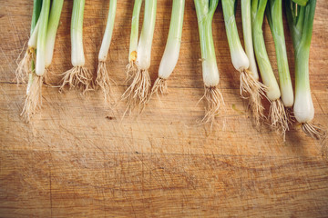 fresh green onions lying on a wooden chopping Board. the view from the top. flat lay. copy space