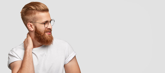Studio shot of satisfied bearded man with trendy haircut, has charming tender friendly smile, keeps hand on neck, being in good mood, stands against white background with free space for your text