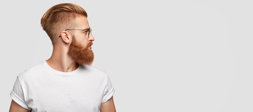 Sideways shot of brutal man with ginger thick beard, trendy hairstyle, looks thoughtfully aside, wears round spectacles and casual t shirt, stands over blank studio background with free space