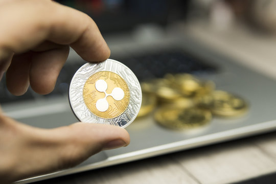 Male businessman hand holding Ripple coin on a background of laptop keyboard and pile of golden coins. Virtual money and Financial growth concept. Trading Mining of Ripples.