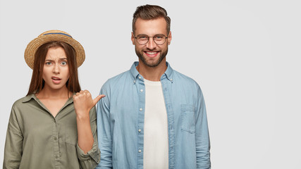 Photo of attractive young girl with puzzled expression points at cheerful guy, express different emotions, stand together against white background with copy space for your advertising content