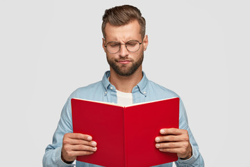 Serious clever young male teacher with trendy haircut, carries red book, tries to understand material, looks with indigant expression, wears round spectacles, stands against white background