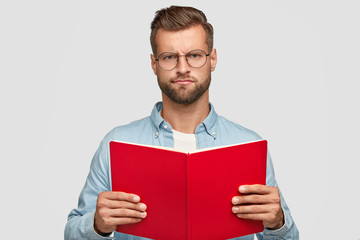 Displeased gloomy male teacher with bristle, uses book for preparing interesting material for lesson, doesnt like his job feels bored of reading wears round spectacles. Clever reader isolated on white