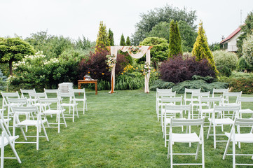 White wedding chairs decorated with fresh flowers on a green grass.
