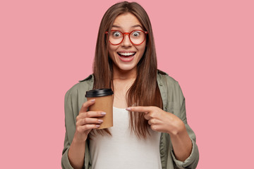 Horizontal shot of cheerful brunette young woman points at takeaway coffee, has joyful expression, advertises aromatic beverage, stands against pink background. People and coffee break concept.