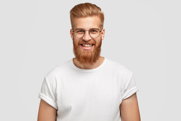 Photo of attractive ginger man with satisfied expression, has thick beard, rejoices promotion at work, dressed in casual t shirt, isolated over white studio wall. People, positive emotions concept