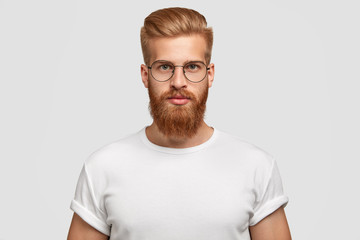 Horizontal shot of attractive hipster looks seriously directly at camera, being self assured, wears big round spectacles, white t shirt in tone with background. Masculinity and style concept