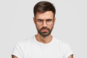 Close up shot of confident strict businessman has thick bristle, looks with gloomy expression, frowns face, wears glasses and casual t shirt, expresses negative feeling, isolated over white background