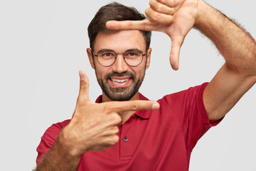 Cheerful satisfied unshaven man makes frame sign with both hands, prepares for being photographed, dressed in casual red t shirt, stands against white background. Look at life from bright angle