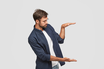 Sideways shot of self assured man demonstrates size or height of something, raises palms in air against white background, wears round spectacles, isolated over white background. Body language concept