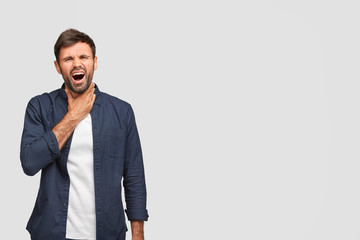 Portrait of displeased guy feels pain, has sick throat, cant speak loudly, has asthma assault, wears casual clothes, stands against white background with free space for your text. I have thore throat