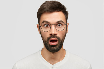 Headshot of stunned young European guy with thick stubble, stares at camera, hears unexpected rumours, wears casual clothes, poses against white background. People and facial expressions concept