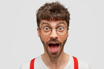 Horizontal shot of funny young man opens mouth with surprisement, popped eyes, wears round transparent glasses, thrilled to recieve awesome news, poses over white background. Emotions concept