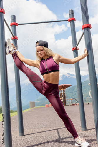 Active blonde female in sports clothes, demonstrates her flexibility