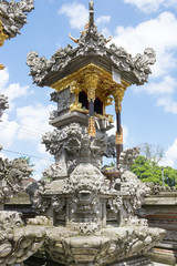 Balinese Hindu family shrine or temple ornately covered with gold showing many effigies of gods and demons.