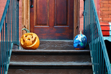 Carved Halloween pumpkins or jack o'lantern on the doorstep in Brooklyn, New York City