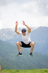 Joyful caucasian man jumping in air at mountains to clouds sky Lifestyle Sport CrossFit and Travel Nature, emotional success concept adventure active vacations outdoor.