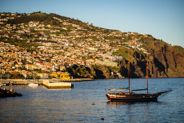 Panoramic view of Funchal on Madeira Island, Portugal. Old sail boat leaving the harbor of Madeira Island.