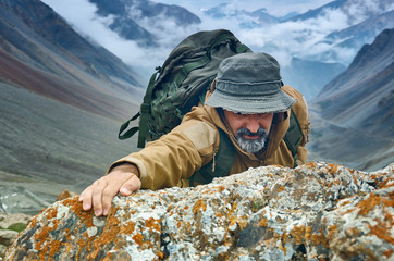 caucasian man with backpack climbing the rock