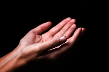 Female hands praying with palms up arms outstretched. Black background. Close up of woman hand. Concept for prayer, faith, religion, religious, worship