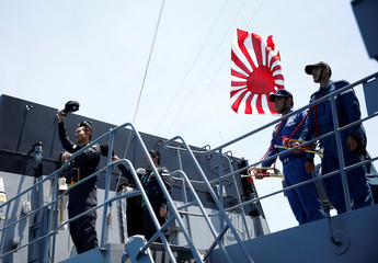 Rear Admiral Tatsuya Fukuda, the commander of Japanese helicopter carrier Kaga flotilla waves to Japanese destroyer Suzutsuki after its joint naval drill with Indonesian patrol boat Kurau in the Indian Ocean