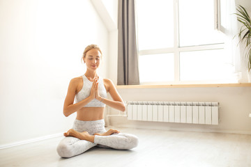 Young caucasian woman wearing white tank top and leggins, meditating while practicing yoga in well lit white training hall. Freedom concept. Calmness and relax, Human happiness.