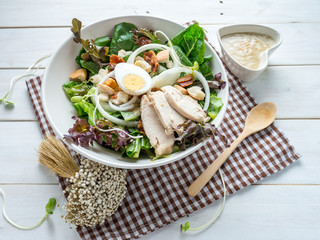 One big ceramic bowl of ceasar salad with ceasar dressing cream.