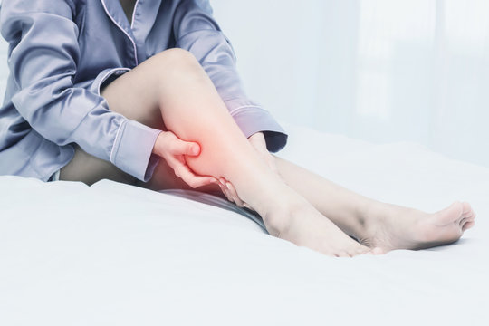 women lag pain on bed in bed room in the morning.