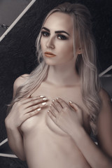 Portrait of naked blond girl who cover one's chest. Fashion Studio Isolated Vertical Photo.