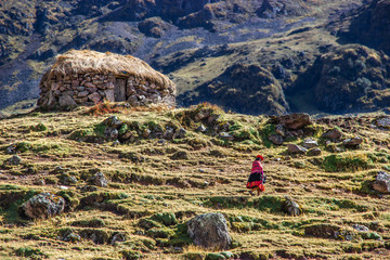 Woman walking past a stone hut along the Inca Trail in Peru