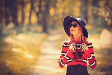 Young girl in a striped sweater with camera and hat in autumn season park