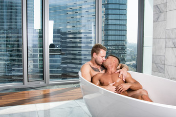 Two sexy guys are washing in the bathroom.