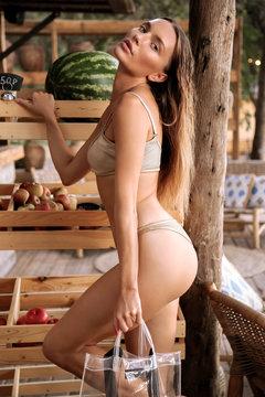 beautiful sensual girl with dark hair in elegant swimming suit making fruit shopping