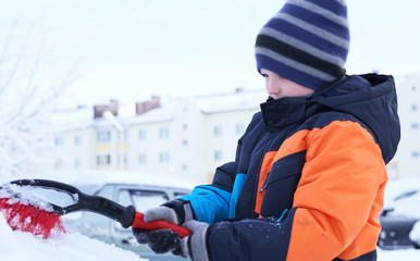 The boy standing near the car and holding a brush. The child cleans the car from snow.