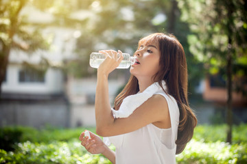 Asian young woman drinking water after workout exercising.