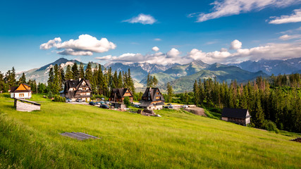 Few houses and wonderful Tatra mountains at sunset in summer