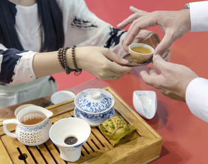 Chinese tea ceremony. The girl pours the tea from the kettle into the cup. The man takes a cup of women's hands.