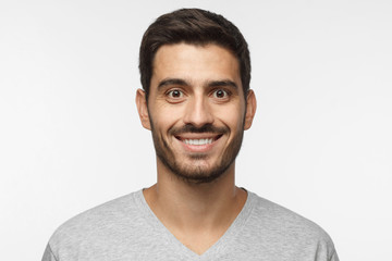 Close up portrait of smiling handsome man in gray t-shirt isolated on gray background