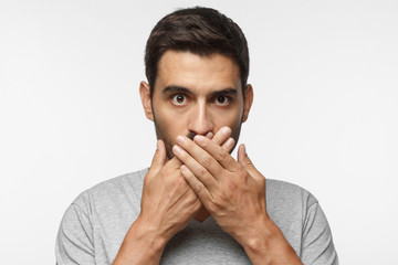 Secret, silence concept. Close up portrait of young man in gray t-shirt covering his mouth with hands isolated on grey background