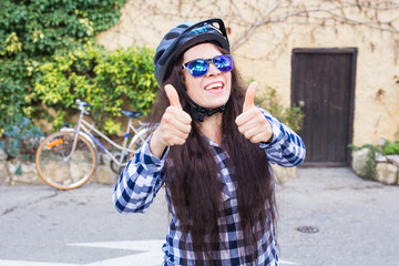 Young smiling woman with helmet and sunglasses showing thumbs up on the background alley and bicycle