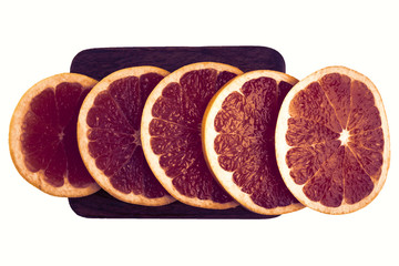 Pink and red grapefruit slices on wooden board. Isolated on white for your design. Top view.