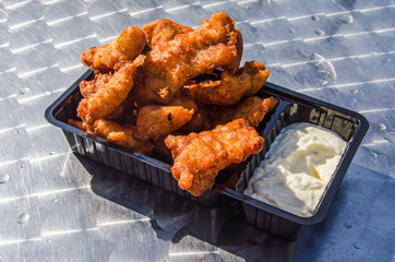 Black plastic box with traditional Dutch fish snack kibbeling (battered chunks of fish) with sauce on a shiny metallic table top