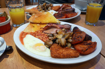 Complete english breakfast for two, with fried eggs, toast, mushrooms,tomato, sausage, beans hash browns and orange juice