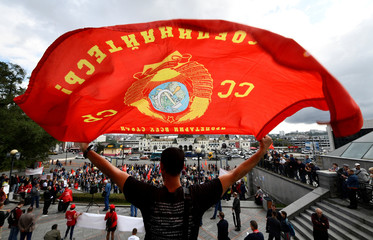 A Russian Communist Party supporter holds a flag during a rally against the vote rigging in the local election in Russia's Primorsky Region and against the pension reform, in Vladivostok