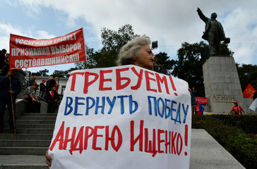 """A woman holds a placard reading """"We demand to hand back the victory to Andrei Ischenko"""" during a rally against the vote rigging in the local election in Russia's Primorsky Region and against the pension reform, in Vladivostok"""