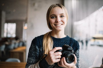 Professional photographer holding digital camera. Smiling hipster woman with beautiful face and blue eyes standing in loft cafe.