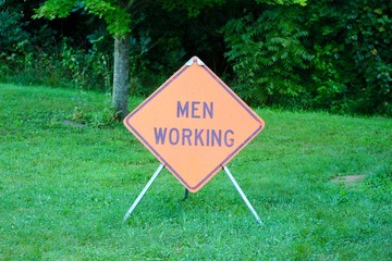 A close view on the men working sign in the grass.